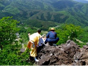 断崖絶壁の岩の上から身を乗り出す覗き修行